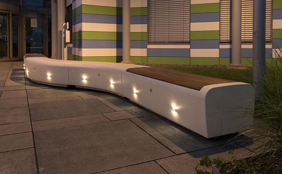 Banco Onda con asiento en madera frente a unas oficinas
